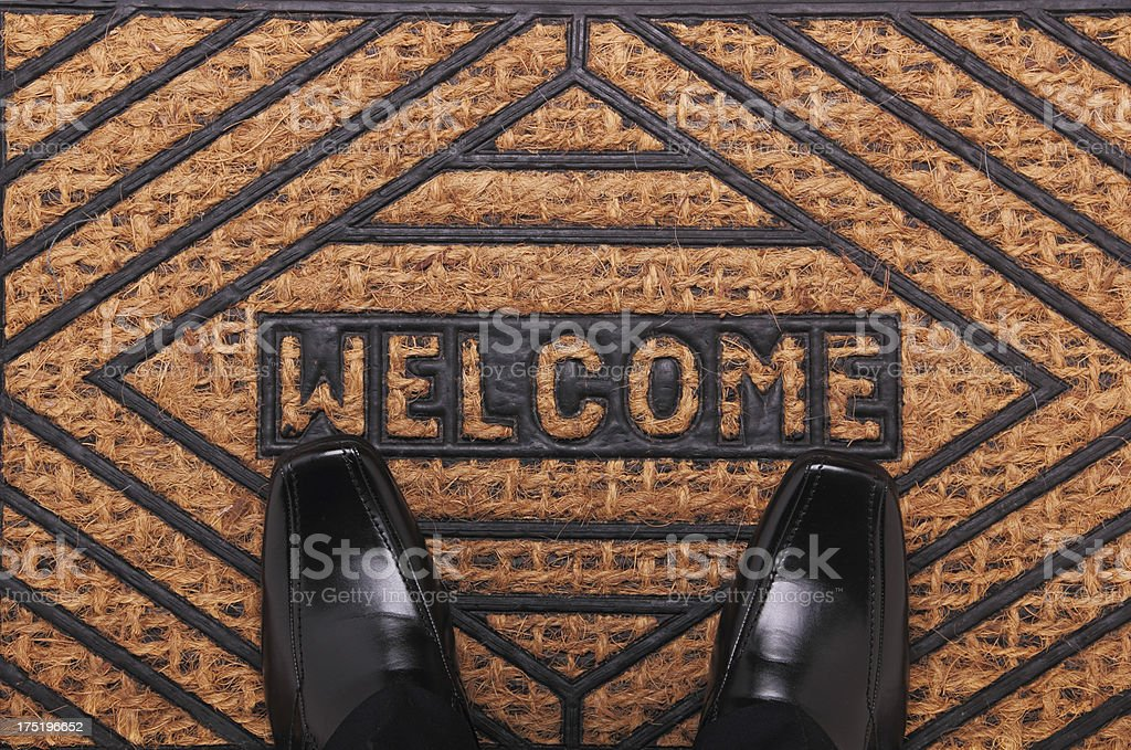 Men's black dress shoes on a brown and black welcome mat stock photo