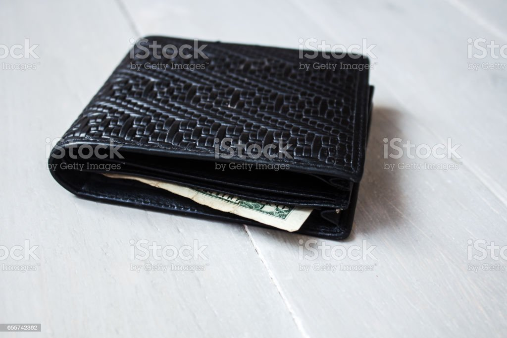 men\'s black wallet with dollar on wooden background