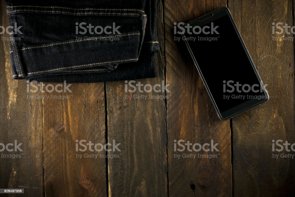 Mens Blue Jeans with Smartphone on Wooden Background. stock photo