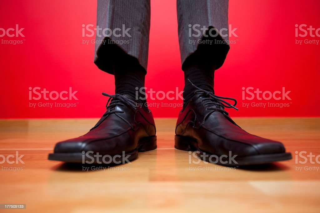Men's business loafers standing on hardwood on a red wall