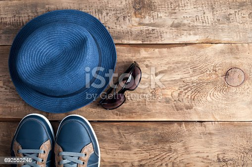istock Men's casual accessories hat, shoes and sunglasses on old wooden background with copy space. Hipster  or traveler outfit. Set of men's clothes 692552246