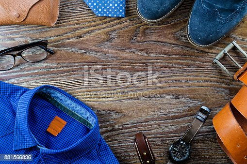 917262406istockphoto Men's casual outfit with man clothing and accessories on brown wooden background 881566836