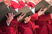 Rochester, England -  July 2018 : Close up of mens choir members holding singing book while performing in a cathedral in Kent, UK