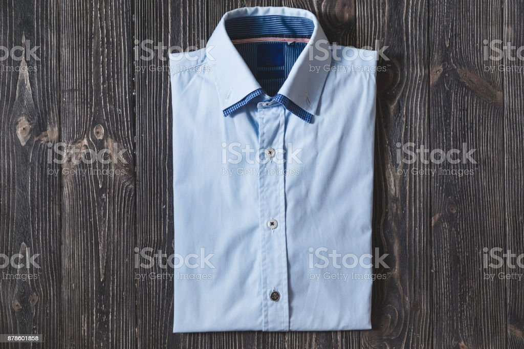 Men's classic blue folded cotton shirt with long or short sleeve on black brutal background. stock photo