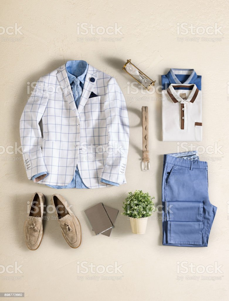 Men's clothing with personal accessories isolated on beige background stock photo