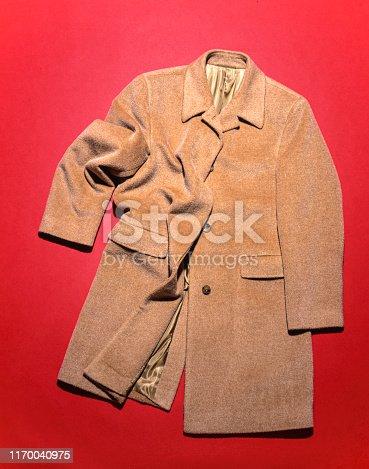 Men's coat on red backdrop, high angle studio shot. camel hair coat