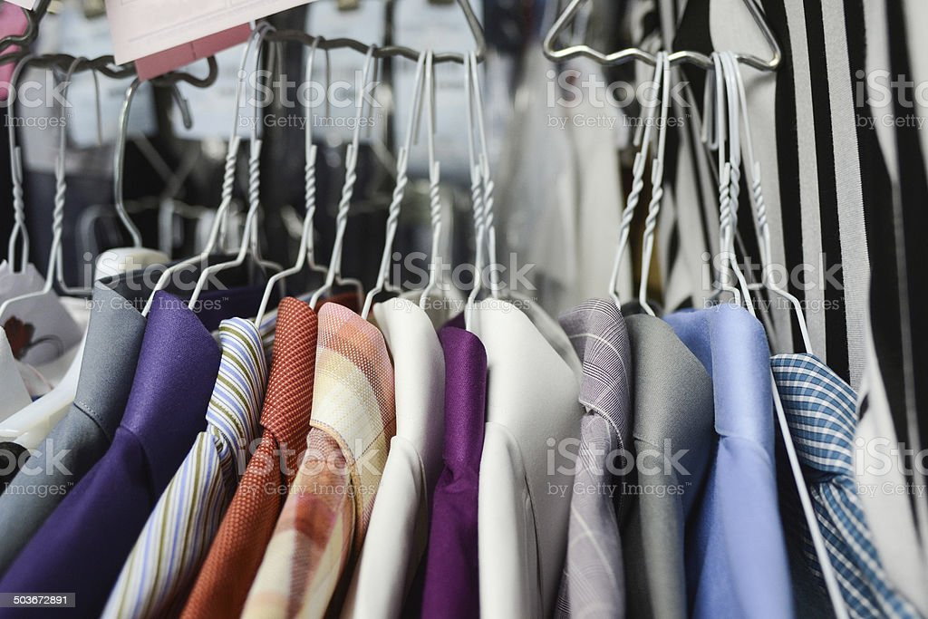 Mens collared shirts hanging in groups at dry cleaners stock photo