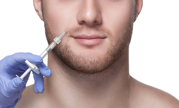 Men's cosmetology. Beautician makes a man a rejuvenation injection procedure on his face. stock photo