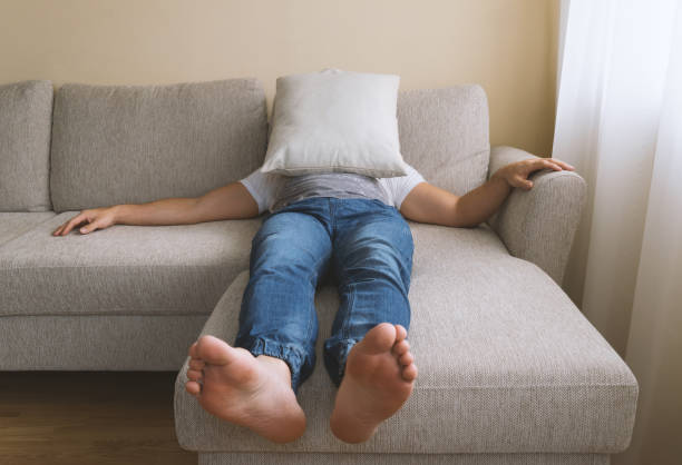 Men's depression concept Faceless adult tired man in blue jogger jeans lying on beige sofa in depression. Men's depression concept, selective focus erectile dysfunction stock pictures, royalty-free photos & images