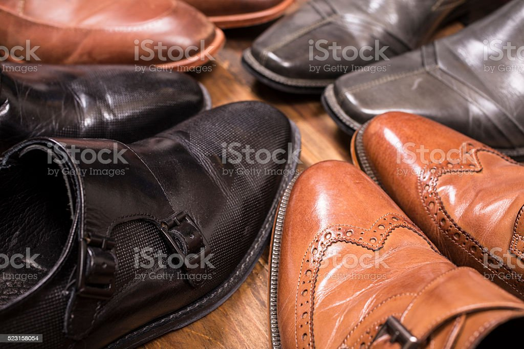 Men's dress shoes lie together in closet.  No people. stock photo