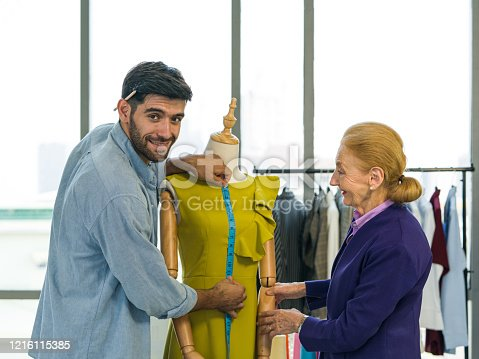Man and woman working in home base cloth design business. Men's dressmaker measuring length of green dress from neck to waist from a mannequins. Elderly customers are waiting anxiously for the size.
