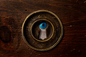 Extreme close-up of men's blue eye looking through the keyhole.