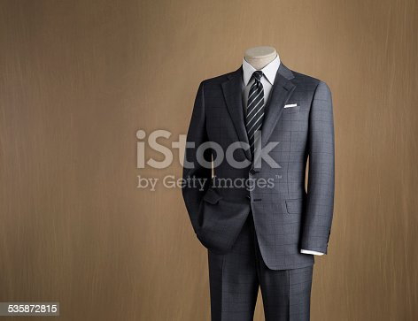 Mens two piece suit displayed on a mannequin photographed against a canvas background
