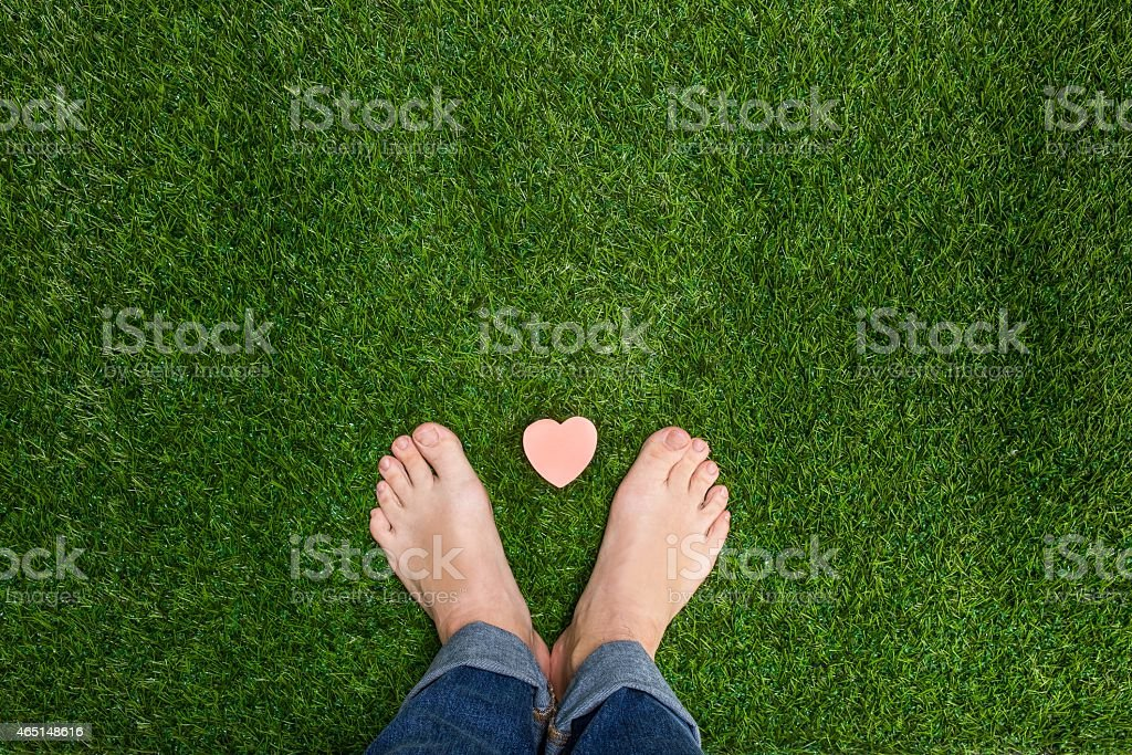 Mens feet standing on grass with small heart stock photo