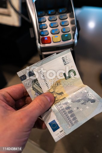 istock Men's hand holding EURO banknotes near a payment terminal POS in a cafe 1140438414