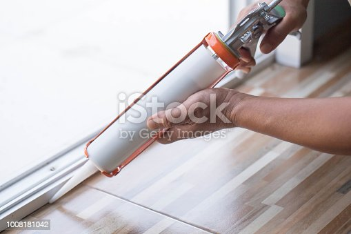 istock Men's hand uses silicone adhesive with a glue gun to repair worn windows. 1008181042