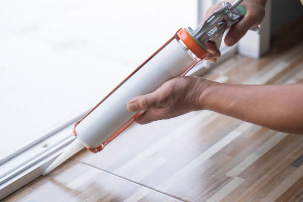 Men's hand uses silicone adhesive with a glue gun to repair worn windows. Men's hand uses silicone adhesive with a glue gun to repair worn windows. silicon stock pictures, royalty-free photos & images