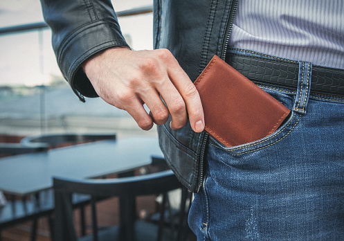 The man pulls a brown leather wallet out of his jeans pocket