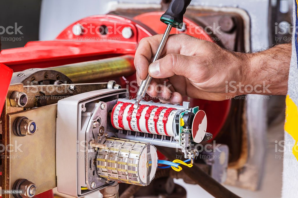 Men's hand with tool on  gas and air mixture regulator royalty-free stock photo
