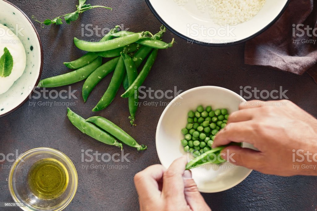 Mens hands cooking vegetarian risotto with green peas, mint and goat cheese. Healthy food concept. Raw ingredients for cooking risotto on dark stone background, top view royalty-free stock photo