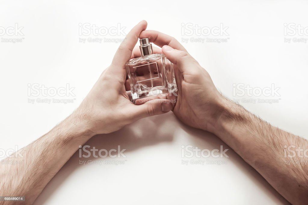 Men\'s hands hold a glass bottle with perfume on a light background