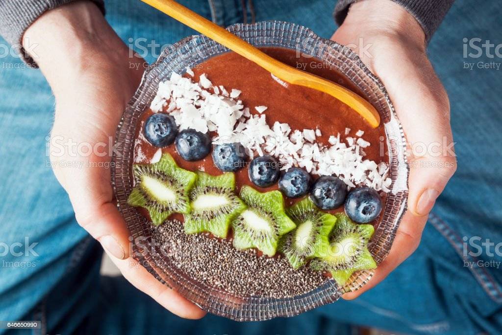 Men's hands hold Breakfast berry smoothie bowl topped with blueberries, kiwi, chia seeds, coconut flakes for healthy breakfast, selective focus stock photo