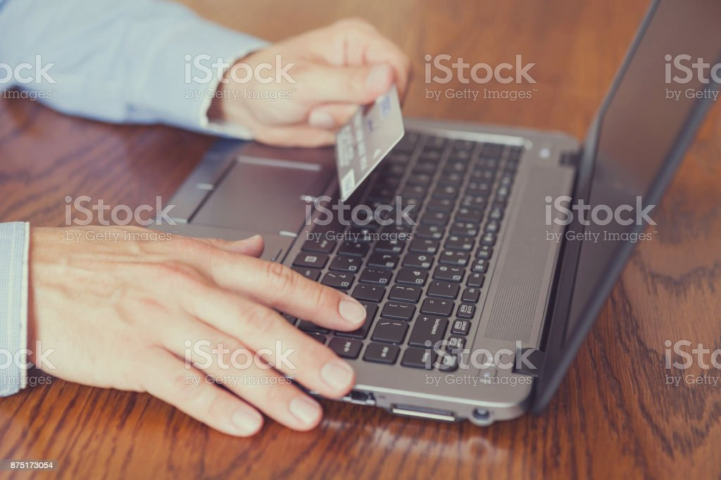 Men's hands holding credit card and using laptop - online shopping stock photo