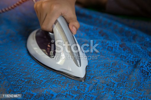 868537890 istock photo Men's hands holding steam iron on ironing board with steaming White iron. 1152424671
