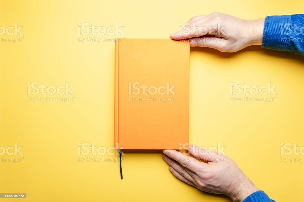 Men's hands in a blue velvet shirt gently hold the literary work with a bookmark in anticipation of reading, which lies on a bright table. The book and the background is yellow.