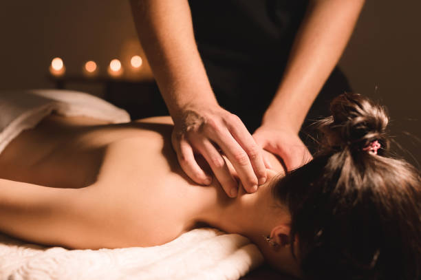Men's hands make a therapeutic neck massage for a girl lying on a massage couch in a massage spa with dark lighting. Close-up. Dark Key stock photo