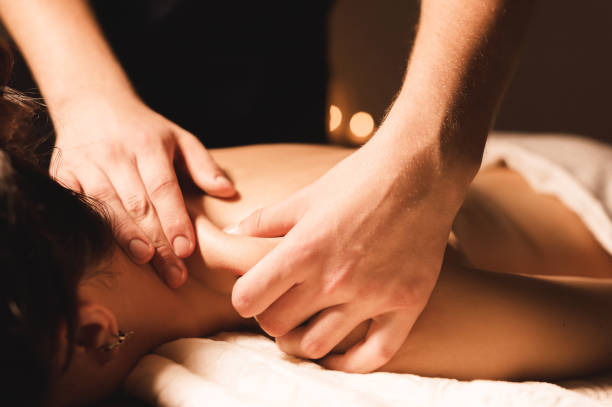 men's hands make a therapeutic neck massage for a girl lying on a massage couch in a massage spa with dark lighting. close-up. dark key - massaggio foto e immagini stock