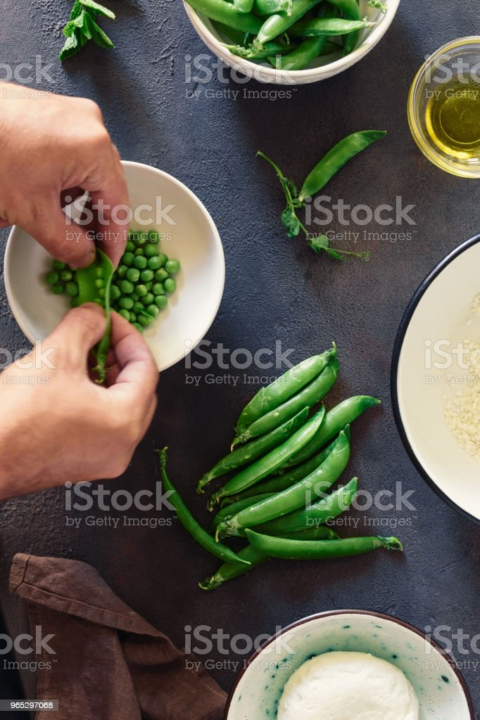 Mens hands prepare vegetarian risotto with green peas, mint and goat cheese. Healthy food concept. Raw ingredients for cooking risotto on dark stone background, top view zbiór zdjęć royalty-free