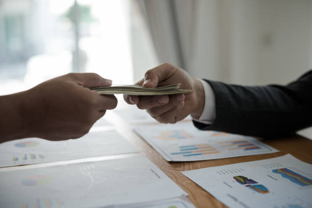 Men's hands, sending money to business travelers. Corruption and bribery concept stock photo
