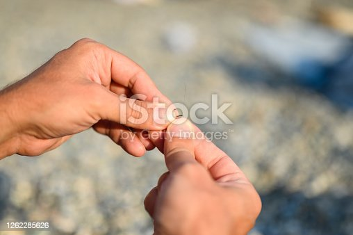 istock men's hands tying a fishing line on a fishing hook. selective focus. step 1 1262285626