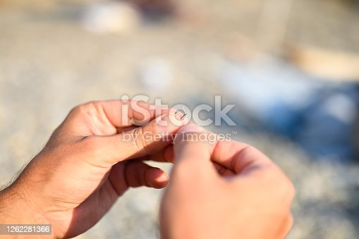 istock men's hands tying a fishing line on a fishing hook. selective focus. step 2 1262281366