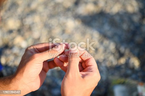 istock men's hands tying a fishing line on a fishing hook. selective focus. step 3 1262284342