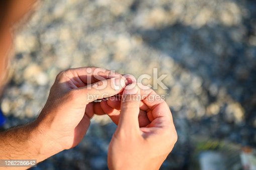 istock men's hands tying a fishing line on a fishing hook. selective focus. step 4 1262286642