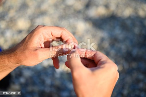 istock men's hands tying a fishing line on a fishing hook. selective focus. step 6 1262280103