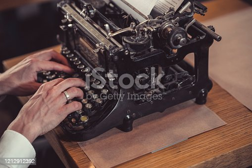 Men's hands typing on a retro typewriter close-up