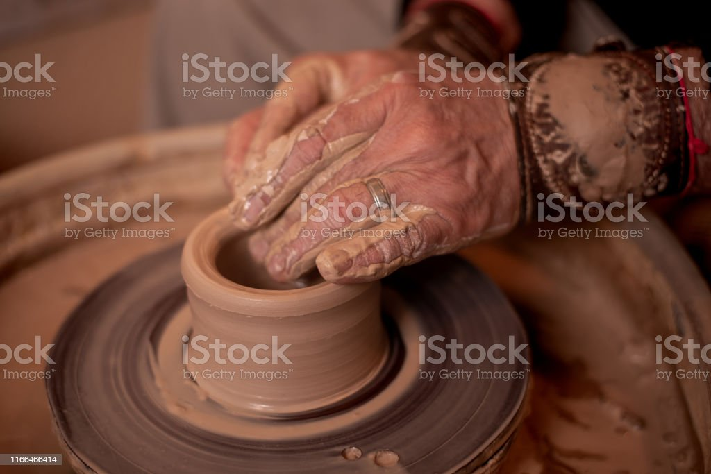 potter\'s hands work with clay, making it a product