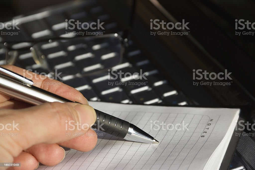 men's hands writing a pen in notebook from computer information royalty-free stock photo
