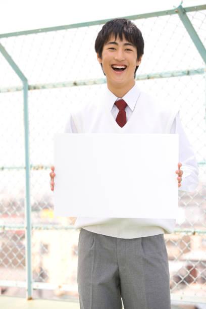 屋根の上のメッセージ ボードを持っている男子中学生 - 中学校 ストックフォトと画像