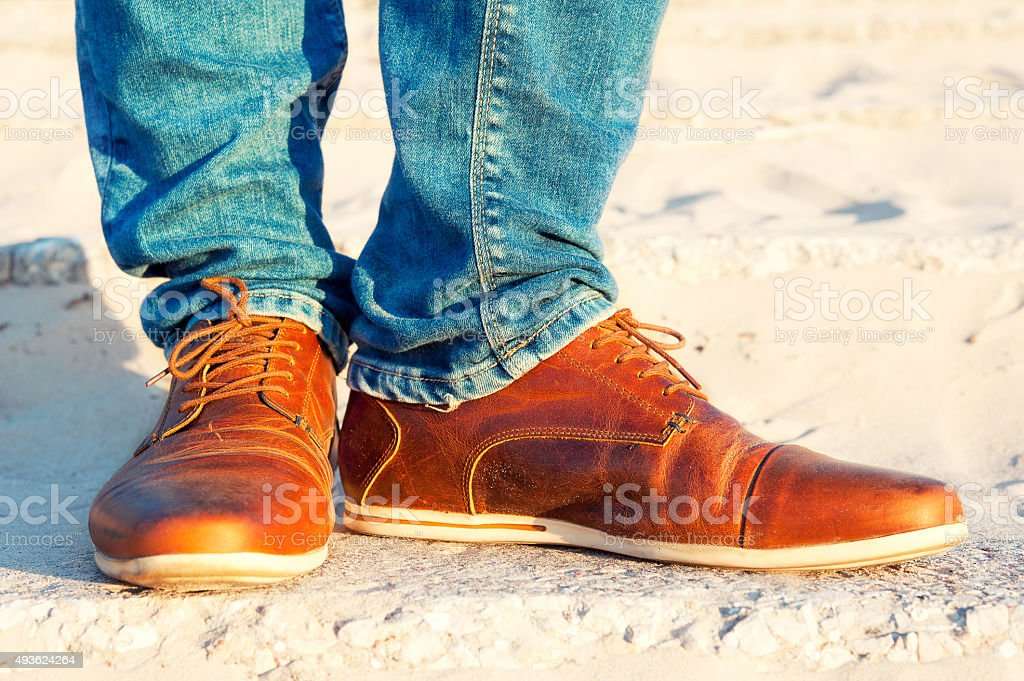 Mens legs in jeans and brown leather elegant  luxury shoes. stock photo
