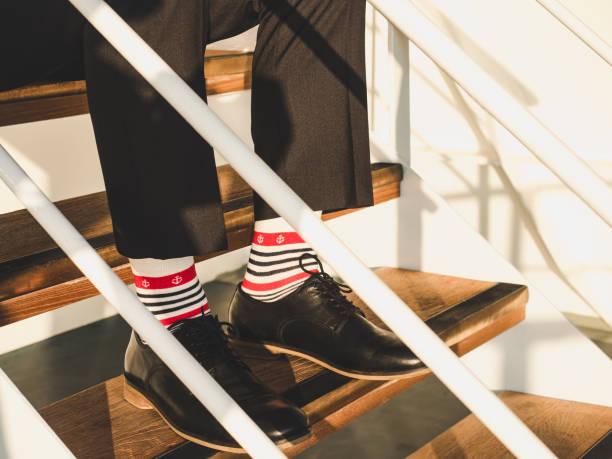 herren beine in eleganten, schwarzen schuhe, dunkle hose und lustige, hell, gestreifte socken mit muster auf dem deck eines kreuzfahrtschiffes - bräutigam anzug vintage stock-fotos und bilder