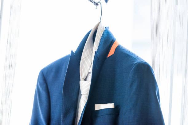 neue marine marineblau herren anzug und krawatte, bräutigam closeup hochzeit vorbereitung isoliert, einstecktuch hängen fenster hänger in hellen raum isoliert - bräutigam anzug vintage stock-fotos und bilder