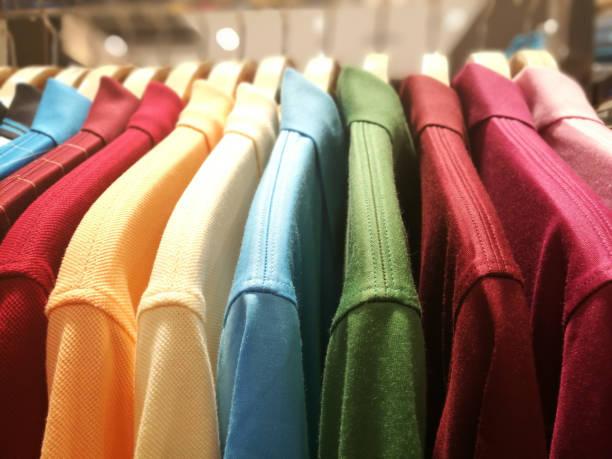 herren hemden in verschiedenen farben auf kleiderbügeln in einem ladengeschäft kleidung - bügelsysteme stock-fotos und bilder