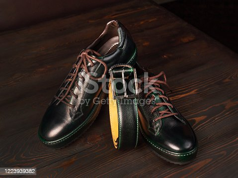 A pair of stylish leather shoes and a trouser belt lie on the surface of dark boards, side view. Close up, selective focus