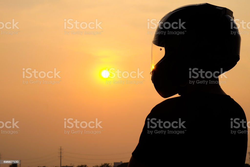 Men's silhouette wearing a helmet looking towards the goal ahead. On a sunset background stock photo