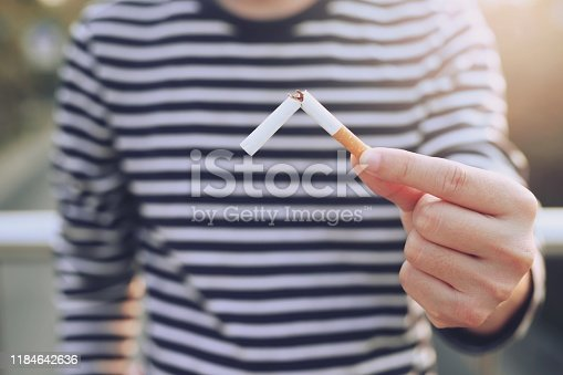 Men's striped shirt using one hand, broken cigarette In order to give up completely