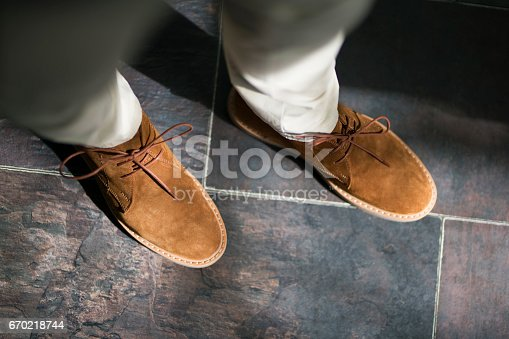 Man's feet in a modern suede shoes.